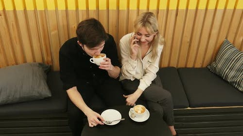 Young Cheerful Woman Talking Via Cell Phone, While Dating in the Coffee Shop