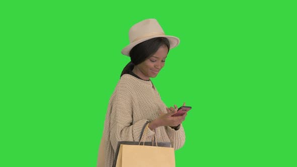 Thumbnail for Happy African American Fashion Girl in Knitted Oversized Sweater and Hat Texting on Her Phone While