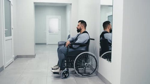 Man with Disability Waiting in Clinic Corridor