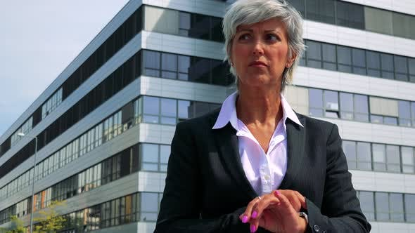 Thumbnail for Business Middle Age Woman Waits Fot Somenone - Company Building in the Background