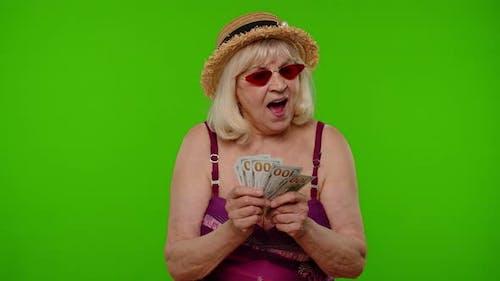 Rich Senior Woman Tourist Counting Cash Enjoying Financial Independence Waving Dollar Bills Income