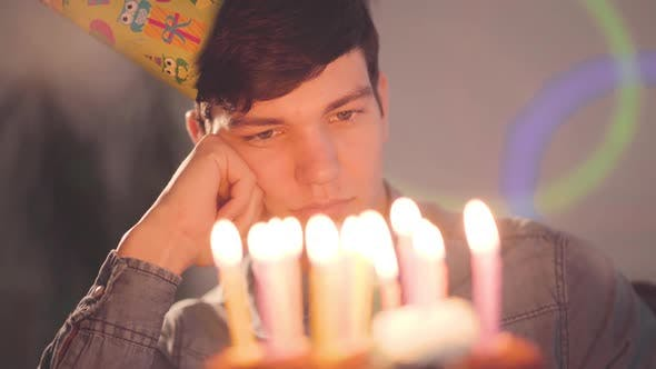 Thumbnail for Lonely Sad Boy Sitting in Front of Little Cake with Lighted Candles Looking on It