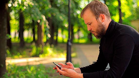 The Young Man With the Phone Sitting in the Park