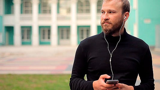 Man Listening to Music with Headphones in a Park