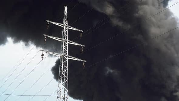 An Electric Tower Stands Against a Background of Black Smoke. A Big Chemical Fire at a Factory