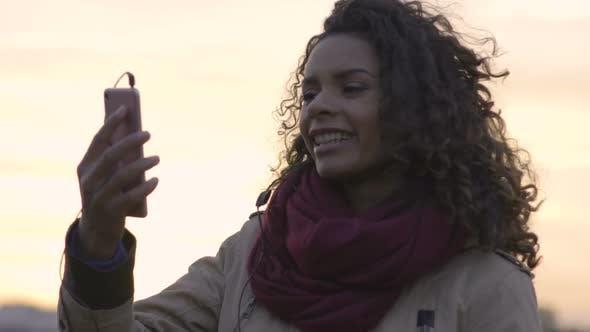 Young Beautiful Woman Watching Favorite Music Clip on Smartphone, Dancing