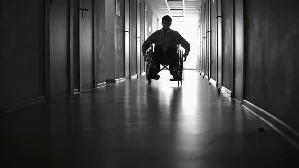Man in Wheelchair Riding along Hallway