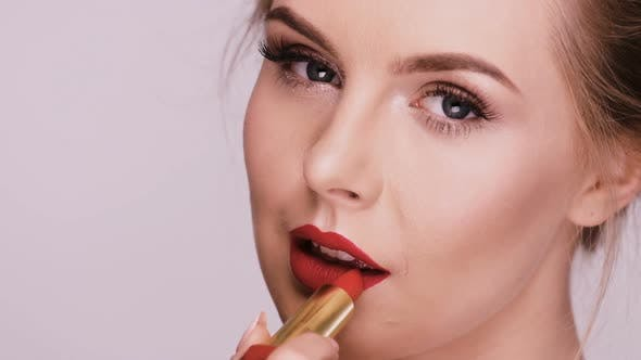 Thumbnail for Close-up of Beautiful Woman Applying Red Lipstick and Smiling