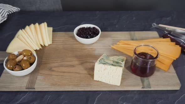 Thumbnail for Arranging gourmet cheese, crakers, and fruits on a board for a large cheese board.