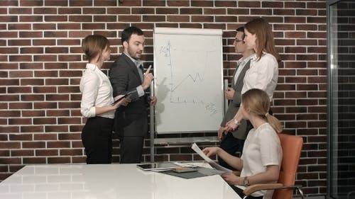 Businessman Giving a Presentation On Flipchart