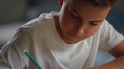 Schoolboy Solving Problems in Notebook, Thoughtful Boy Studying at Home