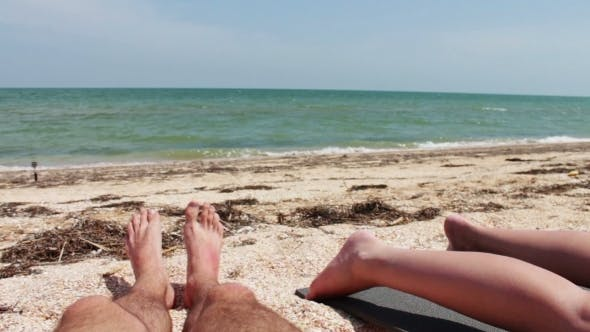 Thumbnail for The Legs Of Two People Are Sunbathe On The Beach