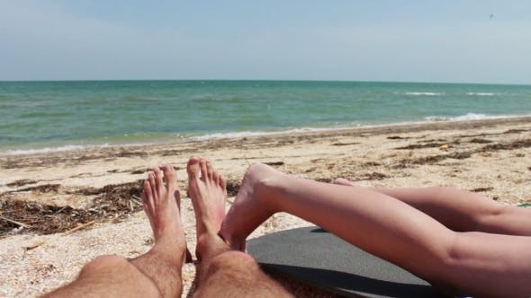 Cover Image for The Legs Of Two People Are Sunbathe On The Beach