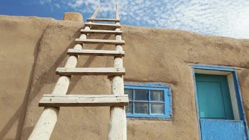 Wooden Ladder Against Adobe Building