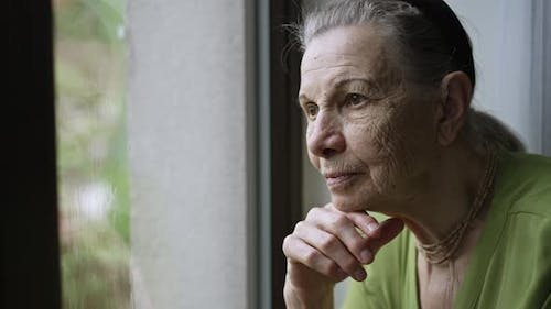 Grandmother Looks Outside the Window