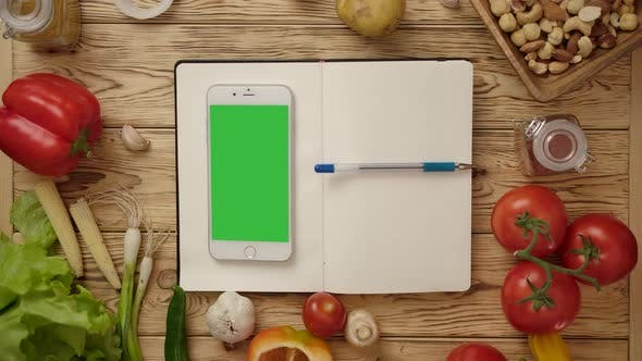 Thumbnail for Pen Rolling on Blank Notebook with Smartphone on Kitchen Table with Vegetables