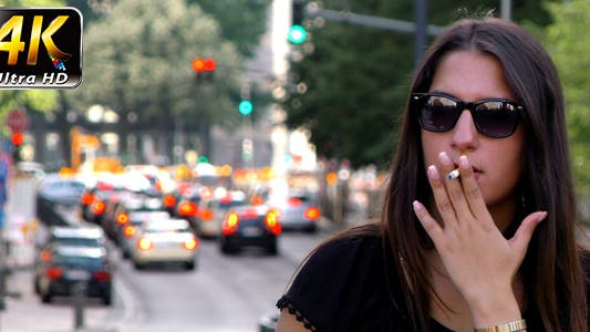 Thumbnail for Woman Smoking and Traffic Behind in City