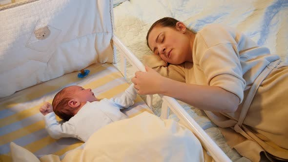 SLeepless Newborn Baby Boy Lying in Crib and Looking on Tired Woman Sleeping in Bed at Night