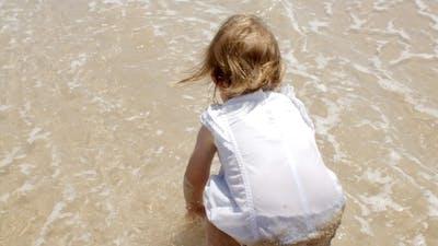 Little Girl Paddling In Shallow Surf