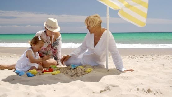 Thumbnail for Grandma  Mom And Little Girl Playing At Beach Sand