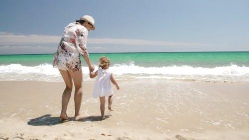 Niedlich Mädchen mit Mama auf die Strand