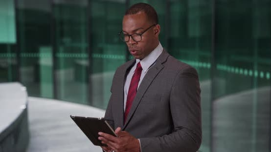Thumbnail for African businessperson looking over financial documents on pad device