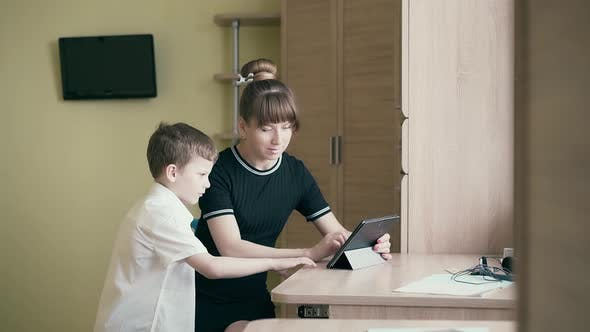 Thumbnail for Tracking: Young Pretty Mother Shows Her Son How To Do Homework, Uses a Tablet Computer.