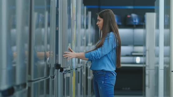 Thumbnail for A Young Woman To Open the Refrigerator Door To Store Appliances and Compare with Other Models To Buy