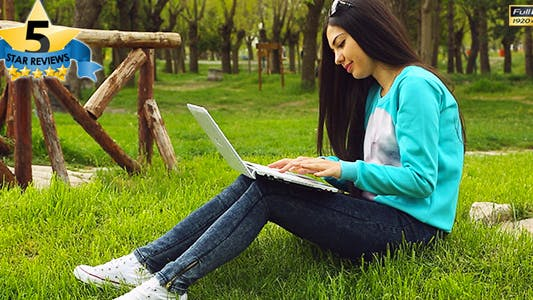 Thumbnail for College Student Sitting in Grass With Laptop