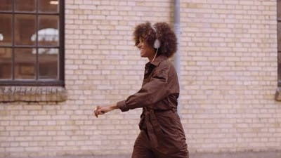 Dancing Woman Laughing As She Listens To Music Through Headphones On Street