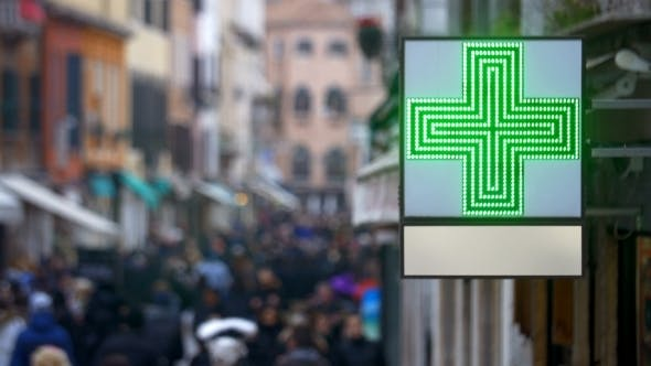 Cover Image for Pharmacy Sign With Green Cross In Busy Street