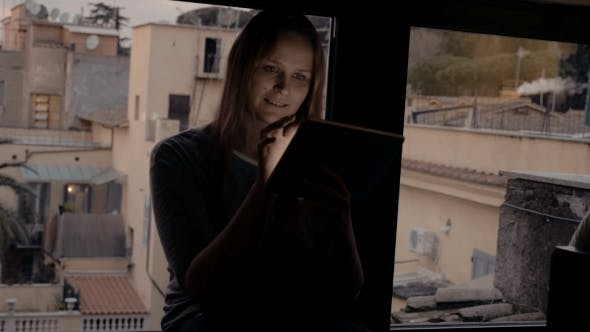 Thumbnail for Woman Using Tablet PC Sitting On Windowsill