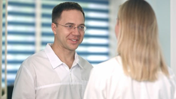 Cover Image for Smiling male doctor in glasses talking to female nurse