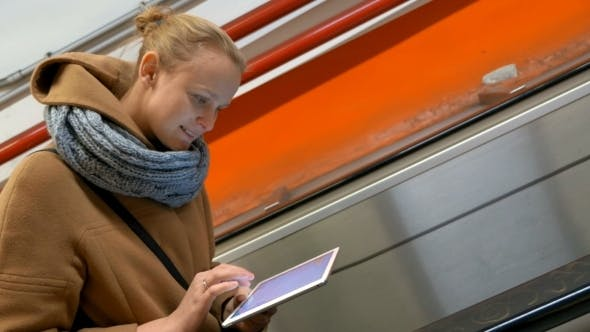 Cover Image for Woman On Escalator Using Tablet Computer