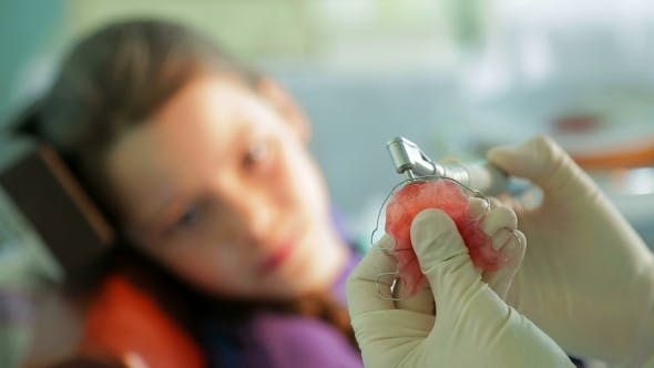 Thumbnail for Girl Watching Orthodontist Correcting Braces For