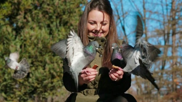 Thumbnail for Cheerful Girl Feeding Pigeons In Park