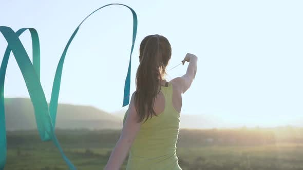 Cover Image for Attractive Female Gymnast Dancing with Blue Ribbon in Outdoors at Sunrise or Sunset