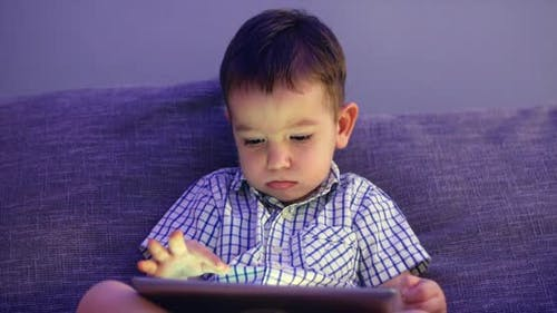 Cute Child Entertaining With Tablet