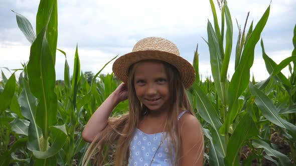 Thumbnail for Portrait of Attractive Small Girl Looking Into Camera and Straightening Her Straw Hat Against the