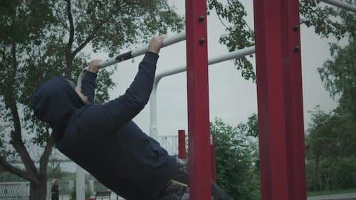 A man pulls himself up on a horizontal bar.
