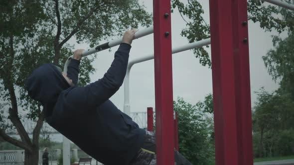 Ein Mann zieht sich auf einer horizontalen Stange hoch.