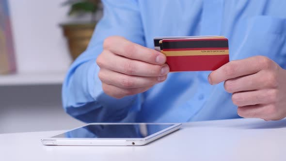 Thumbnail for Man Shopping Online Using Digital Tablet and Gold Credit Card. Online Shopping. Close Up