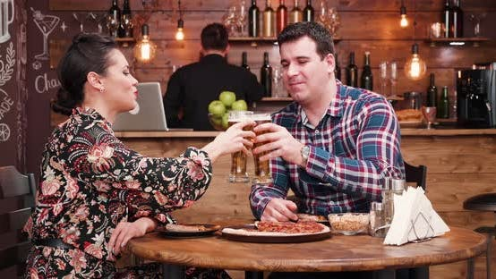 Cover Image for Caucasian Couple Eating Pizza and Drinking Beer