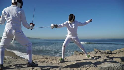 A man and woman fencing on the beach