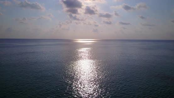 Tropical birds eye travel shot of a white sandy paradise beach and aqua blue ocean background in 4K