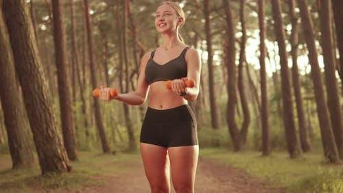 Sportswoman Lifts Dumbbells in Open Nature