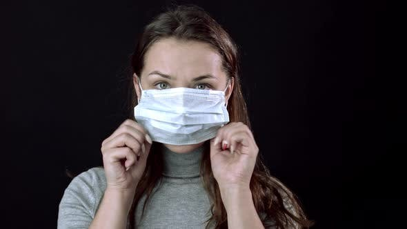 Thumbnail for Beautiful Woman Puts on Medical Mask. Black Background. Global Pandemic Covid-19