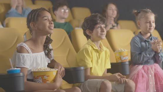 Angle View of Excited Children Watching Film in Cinema with Adults Enjoying Movie at the Background
