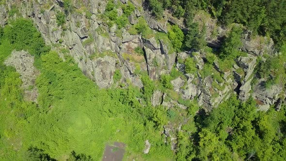 Thumbnail for Aerial: Flying with Turning the Camera. View of the Foot of a Stone Mountain with Coniferous Forest