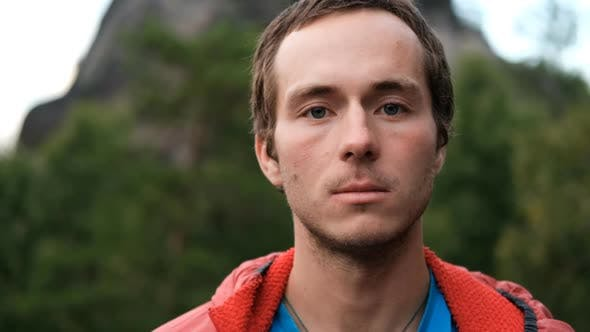 Slow Motion Portrait of a Young Male Hiker Looking at the Camera and Smiling
